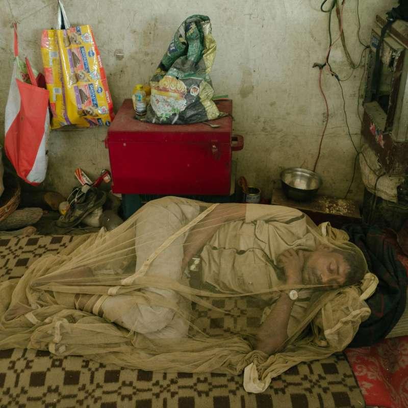 生活在被污染的河流和露天下水道附近的人,很容易患上登革熱,睡在蚊帳裡可以提供一些防護。(圖/言人文化提供)