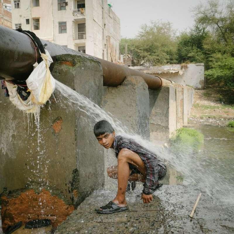 小拾荒者正在排水管旁沖洗,他一直在搜尋能賣錢的垃圾。(圖/言人文化提供)