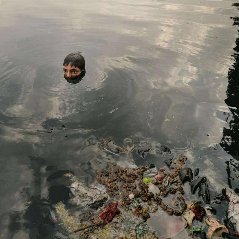 拾荒者裡不乏小孩子,他們在被污染的亞穆納河裡搜尋從橋上扔下的宗教物品。從硬幣到小金屬雕像,都可以拿到廢品站換錢。(圖/言人文化提供)