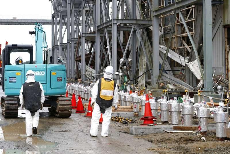 負責除污善後的工人正在福島核電廠工作。(美聯社)