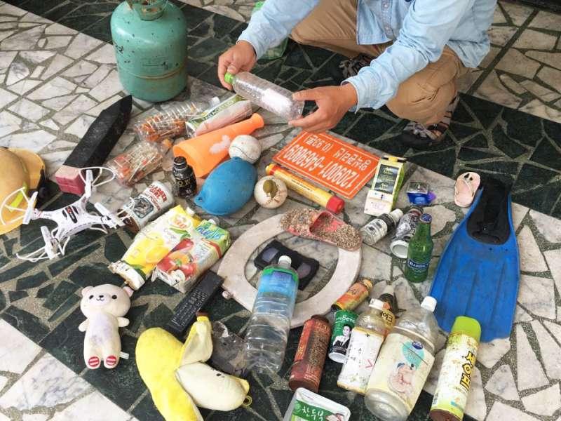 陳大哥展示他的戰利品:他手上拿著印尼來的瓶中信,第上攤開的則有布偶、馬桶蓋、來自各國的飲品包裝、保險套、蛙鞋、空拍機等。什麼都有,什麼都不奇怪。(圖/鐘敏瑜攝)