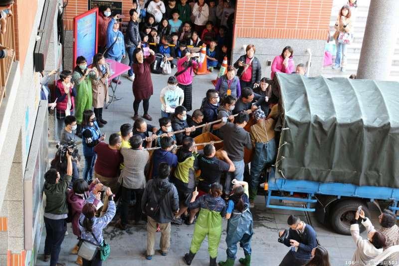 觀度國小師生和救援志工合力抬起超過300公斤的「關關」。(台北市政府提供)