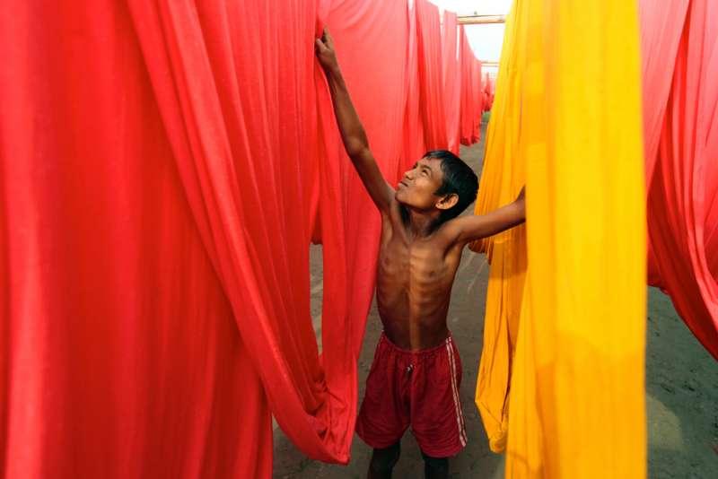 孟加拉國達卡,一名兒童在一服裝漂染廠工作。根據國際勞動組織的統計顯示,孟加拉國大約有320萬童工。(圖/言人文化提供)