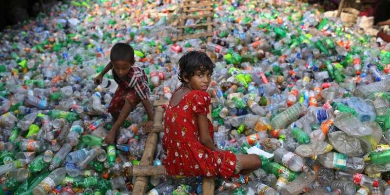 孟加拉國達卡,13歲的女孩Sharmin在塑料回收工廠里工作,旁邊的小男孩則在塑料瓶堆裡玩耍。(圖/言人文化提供)
