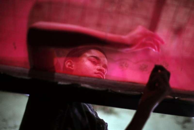 尼泊爾加德滿都,一名移民男孩在紗麗工廠工作。(圖/言人文化提供)