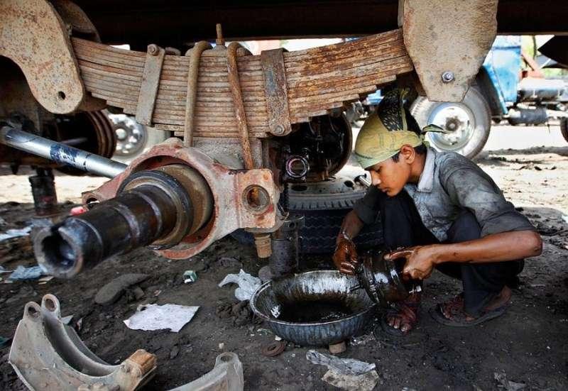印度新德里,一名男孩正在清洗貨車的零部件。(圖/言人文化提供)