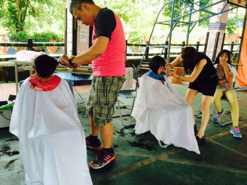 克難場地裡,這群義剪團簡單布置就開始剪髮,就連洗頭也是只能就近找洗手台解決。(圖/大作提供)