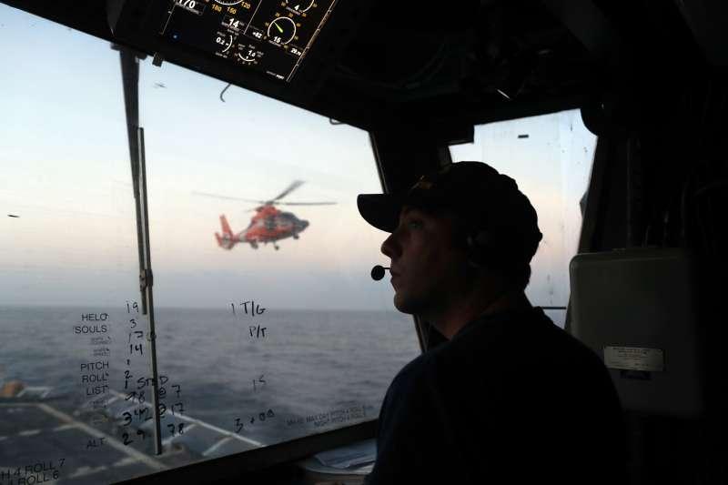 美國海岸防衛隊的執法人員在巡邏艦上與直升機飛行員進行溝通。(AP)