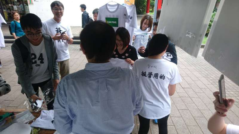 台大自主聯盟今天在校內擺攤,販售挺管的T恤,管中閔也現身幫支持者簽名。(讀者提供)