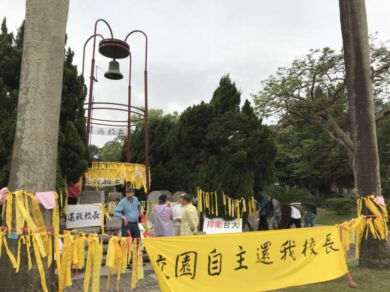 20180503_部分台大師生在傅鐘前綁黃絲帶抗議,繫布條「校園自主還我校長」,力挺大學自主。(吳尚軒攝)