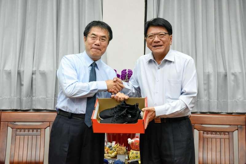 20180518-屏東縣長潘孟安贈送台南市長候選人黃偉哲一雙球鞋,鼓勵黃勤跑基層、傾聽民意。(屏東縣政府提供)