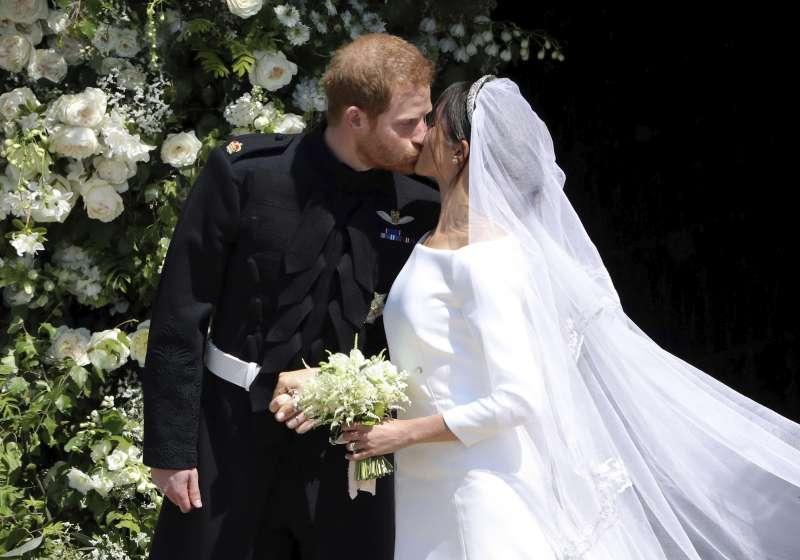 英國哈利王子與梅根於19日舉行婚禮,婚禮儀式結束後,兩人在準備搭馬車前深情一吻(美聯社)