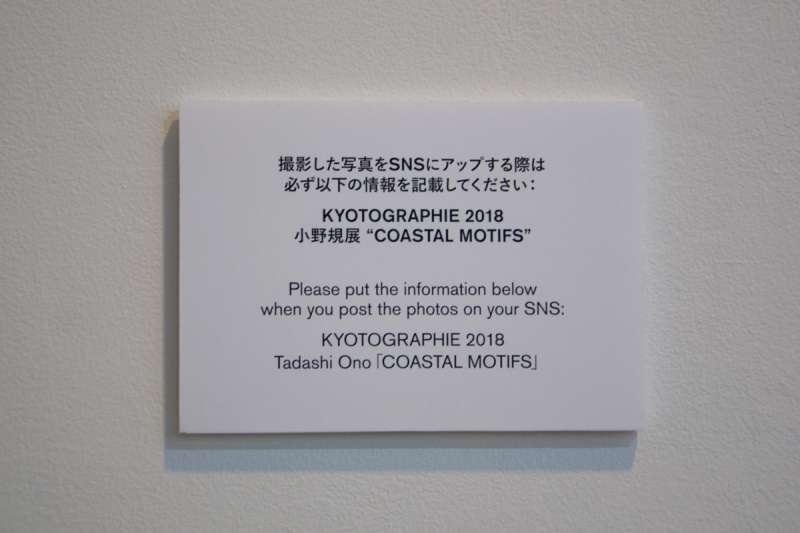 """小野規展覽會場中放置的告示,指出「攝影的照片若要上傳至SNS時,請務必寫上以下說明:『KYOTOGRAPHIE 2018 小野規展 """"COASTAL MOTIFS"""" 』」(圖/想想論壇提供)"""