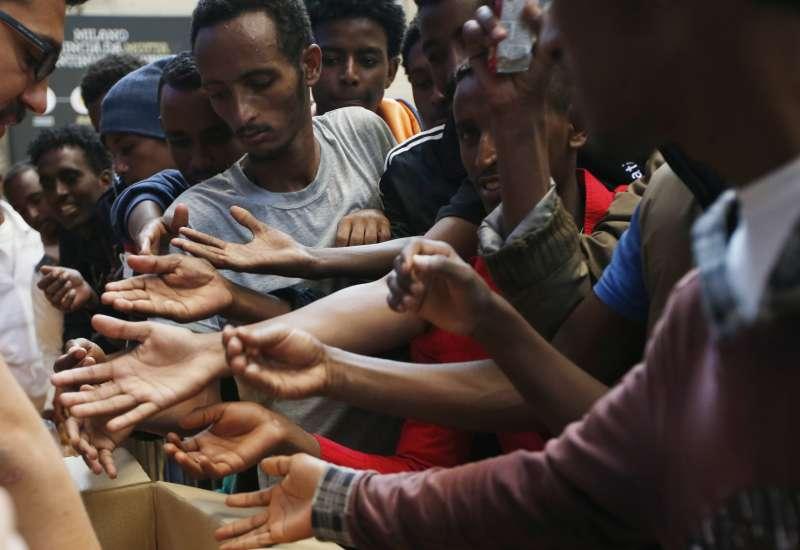 難民在義大利米蘭的火車站領取食物(美聯社)