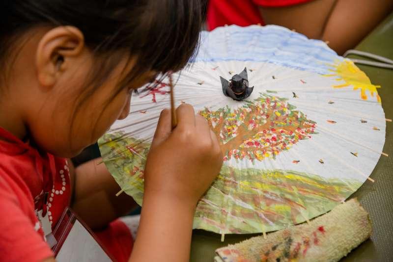 在美濃客家文物館中用小手畫出屬於個人特色的紙傘,小朋友一筆、一筆慢慢繪出家鄉的樹、家鄉的草原。