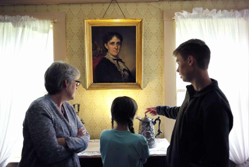 奧爾柯特的故居「果園屋」後來變成歷史博物館,遊客站在奧爾柯特的肖像畫前方(AP)