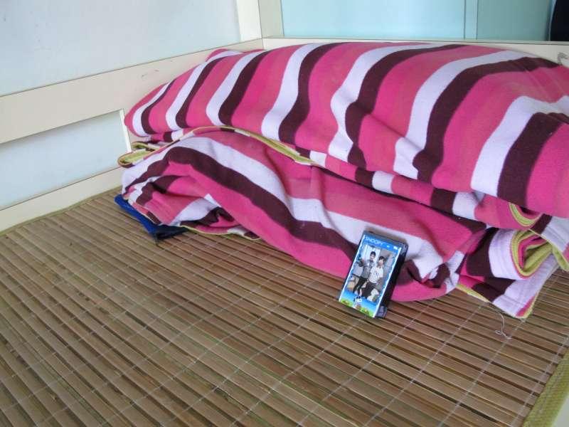 浩浩放在床頭邊上的與兄弟小麥的合影每天起床後放在床頭(圖/曹嘉真攝).jpg