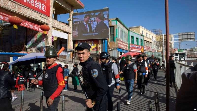 警察在新疆和田大巴扎外的地段巡邏。(美聯社)
