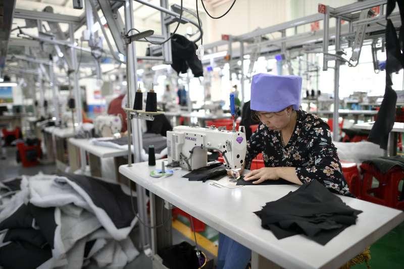 工人在中國寧夏同心縣扶貧產業園一家製衣企業製作成衣(新華社)
