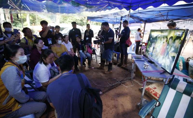泰國受困足球隊員與教練的家屬看著電視螢幕上的受困人員影片(AP)