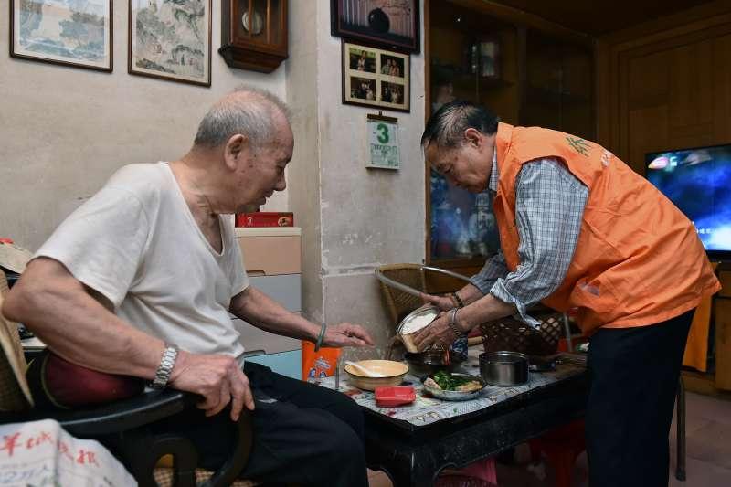 廣州六榕社區的志願者黃湛泉(右)為行動不便的居家老人送餐上門。(新華社)