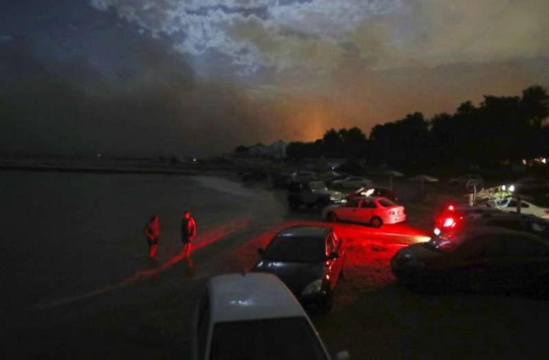 希臘森林大火,人們往海邊逃。(美聯社)