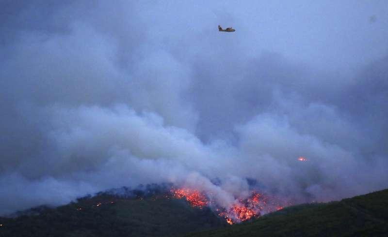 希臘森林大火,直升機在馬蒂村上空徘徊搜救。(美聯社)