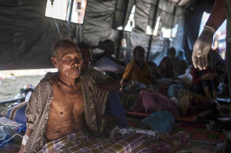 印尼龍目島卡亞甘地區受災嚴重,一名老人正在帳篷搭成的臨時醫院休息(AP)
