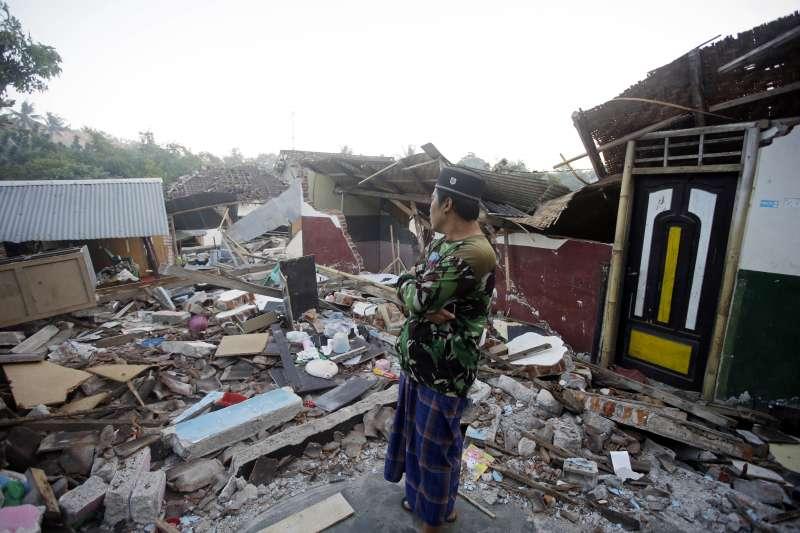 印尼龍目島北部在5日強震中受災嚴重,一名居民望著倒塌的家園(AP)