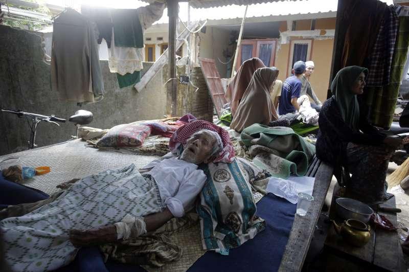 龍目島西北部的科凱村在5日強震中受災嚴重,一名受傷的老人躺在臨時庇護所休息(AP)