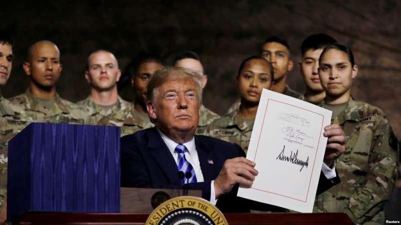 川普總統在紐約州德拉姆堡美國陸軍第10山地師的軍人面前舉起他剛剛簽署的《2019年國防授權法》。(美國之音)