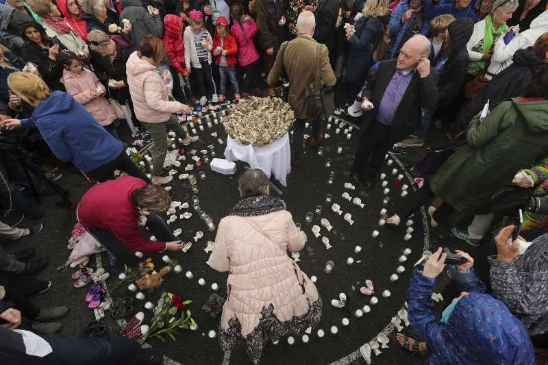 抗議者在小白棺旁放下小鞋子,紀念這些沒能長大的孩子們。(AP)