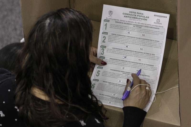 哥倫比亞舉行反貪公投,選民聚精會神研究選票上的提案。(AP)