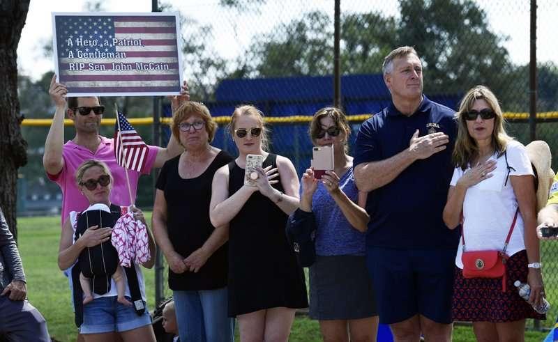 許多美國民眾在烈日之下前來美國海軍學院周邊,送馬侃最後一程,當中有人手持悼念標語「您是英雄、愛國者、紳士,馬侃先生安息!」(AP)