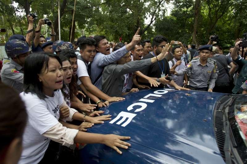 緬甸仰光法院3日宣判後,社運人士與記者試圖阻擋警車載著瓦隆與吳覺梭離開法院(AP)