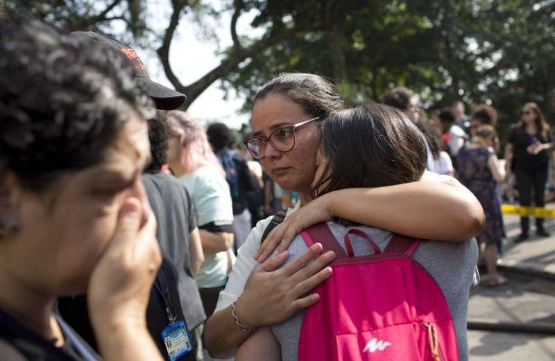 巴西國家博物館2日發生大火,無數珍貴文物付之一炬,博物館工作人員在館外傷心相擁(AP)