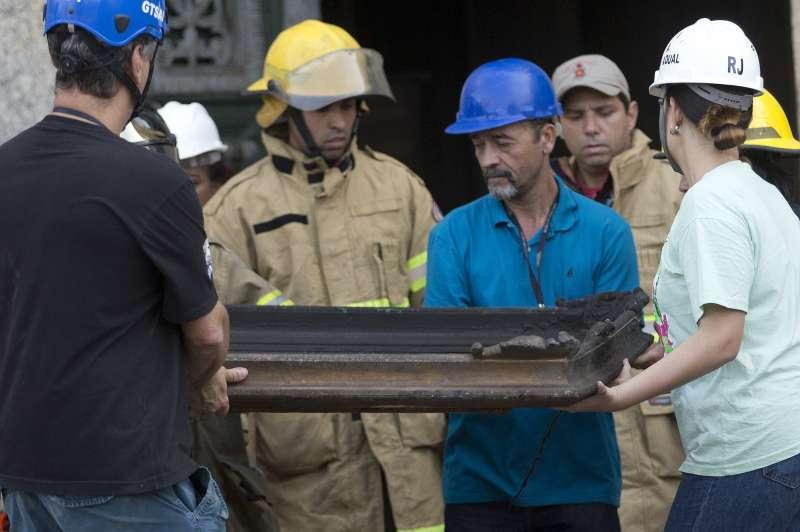 巴西消防人員與國家博物館工作人員從火場內抬出一幅燒毀的畫作(AP)