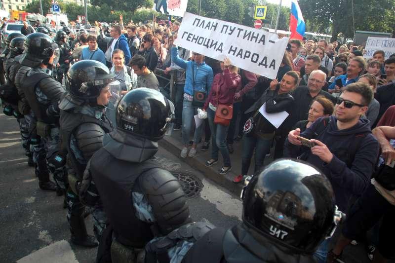 俄羅斯各地9日舉行示威活動,抗議政府的退休金改革計畫,群眾手持的標語寫著:「普京的計畫是對人民的屠殺」。(AP)