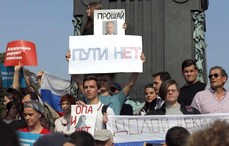 俄羅斯各地9日舉行示威活動,抗議政府的退休金改革計畫,畫面上方的普京頭像寫著「再見」的字樣。(AP)