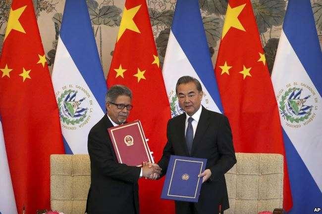 薩爾瓦多外長卡斯塔內達(左)和中國外長王毅在北釣魚台國賓館舉行的建交儀式上手持建交協定書。(2018年8月21日)。(美國之音)