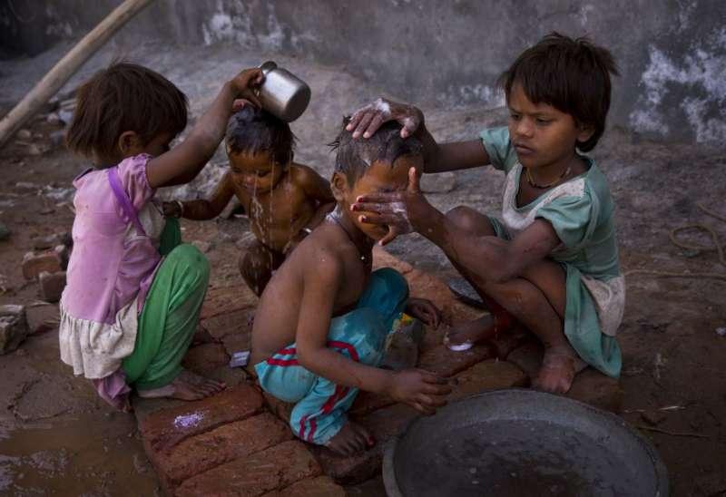 印度新德里郊區的酷暑,2名年幼女孩在幫弟妹沖澡(AP)