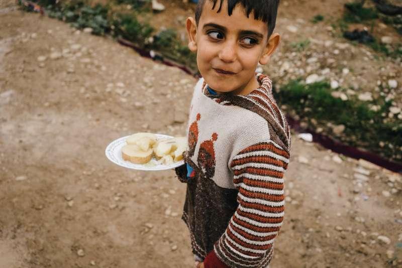 2016年1月,伊拉克北部難民營的一名敘利亞男童拿著一盤水煮馬鈴薯。聯合國指出,「營養不良」是數百萬難民面臨的一大威脅(AP)