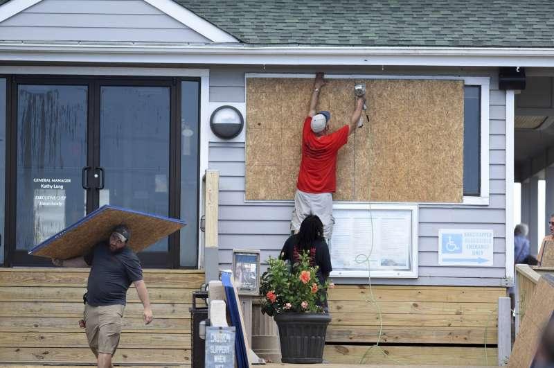 颶風來襲前,北卡羅來納州居民用層板釘牢門窗。(美聯社)