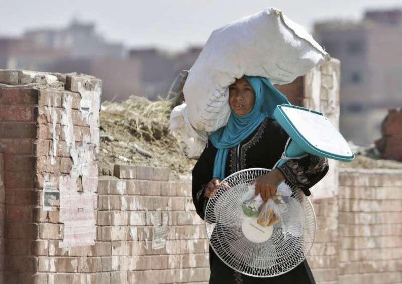 2015年8月,埃及開羅一名婦女帶著電風扇走在街上(AP)