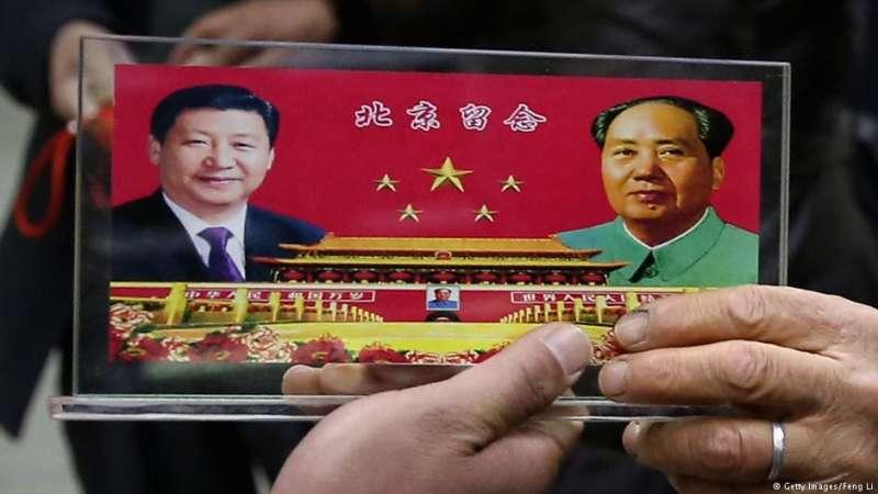 2013年中共黨代會期間,商販在北京市中心區域向遊客兜售印有毛澤東和習近平頭像的紀念品。(DW)