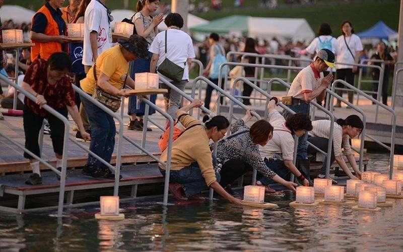 民眾可以把心願或想傳達給已逝親友的話,寫在真如水燈上,施放到水面傳達出去。(圖/真如苑)