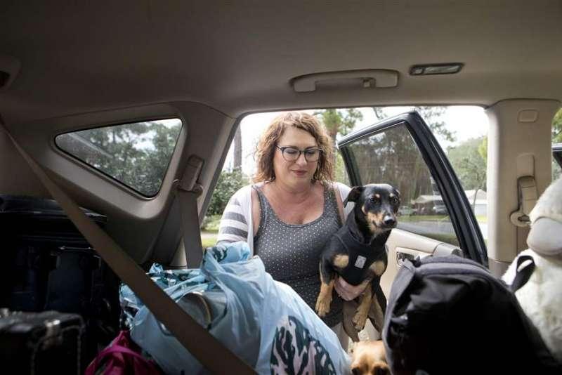 颶風「麥克」來襲,美國佛州西部貝郡的居民洛格絲登帶著寵物狗兒與貴重物品,準備與丈夫一起駕車撤離家園(美聯社)