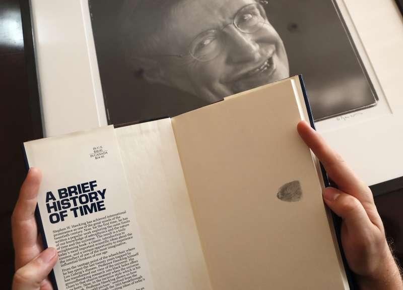 拍賣品之一,霍金在《時間簡史》內頁捺指印取代簽名。(美聯社)