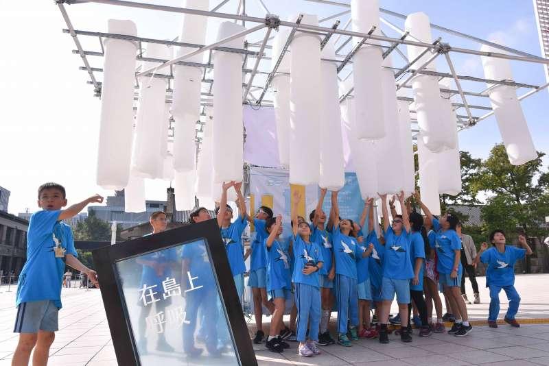 五十萬作品「在島上呼吸」在鷹架上裝設了50多根空氣柱,當機器感應到人進入這個場域,空氣柱便會給予上下竄動的反饋。將平常最被需要也最容易被忽略的空氣具象化,喚起大家對空氣的重視。