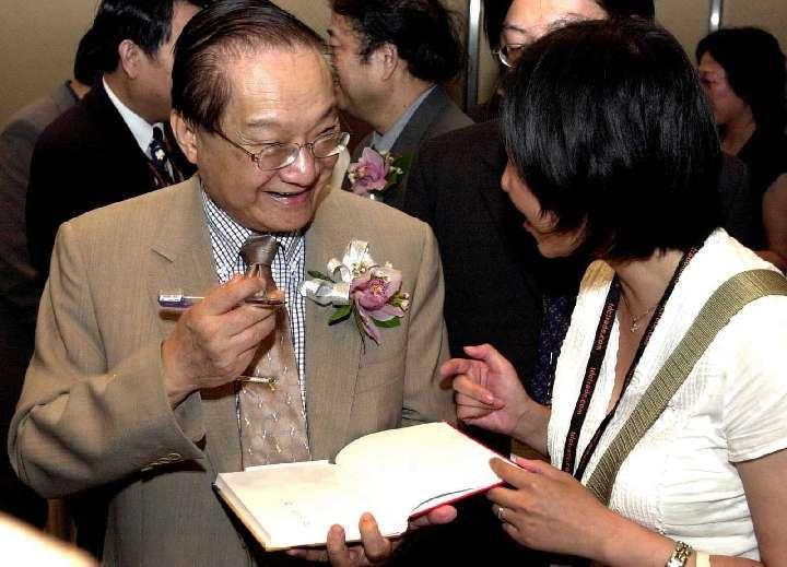 這是2001年7月22日,金庸(左)在2001香港書展上為讀者簽名留念。(新華社)